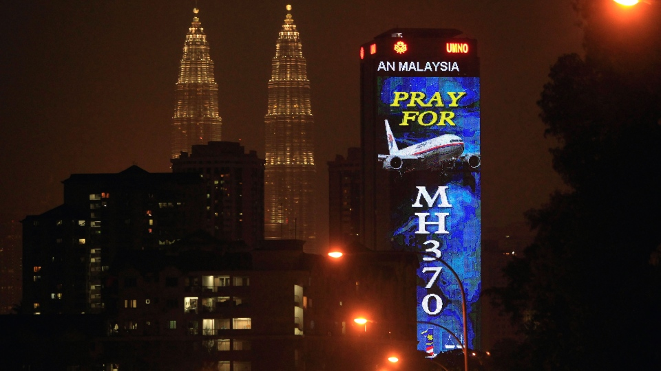 An office building is illuminated with LED lights displaying 'Pray for MH370' next to Malaysia's landmark Petronas Twin Towers in Kuala Lumpur, Malaysia, Wednesday, March 19, 2014. (AP / Lai Seng Sin)