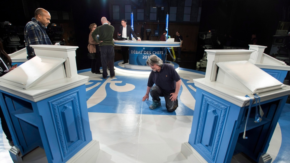 Technicians work on the set in preparation for the leaders' debate as part of the Quebec provincial election, Thursday, Wednesday, March 19, 2014 in Montreal. (THE CANADIAN PRESS / Paul Chiasson)