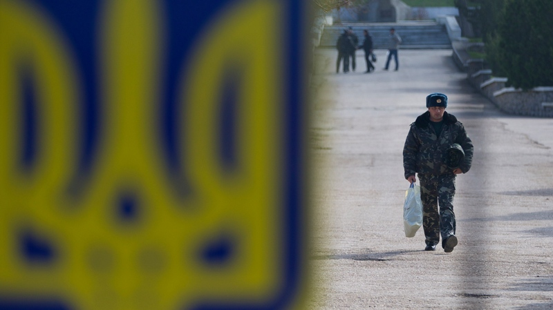 A Ukrainian air force officer walks carrying his belongings at the Belbek airbase, outside Sevastopol, Crimea, on Thursday, March 20, 2014. (AP Photo/Ivan Sekretarev)