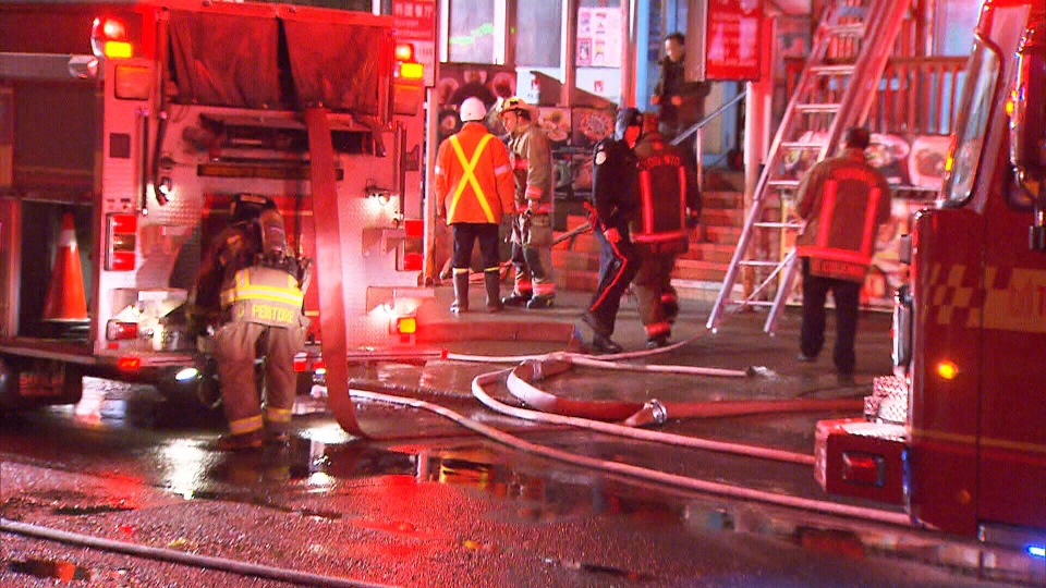 Fire crews inspect the scene following a three-alarm fire at a rooming house in Toronto's Kensington Market, early Thursday morning, March 20, 2014.