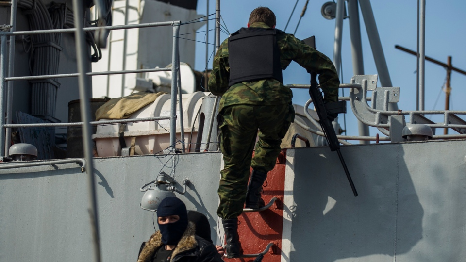 Men in unmarked uniforms and wearing masks, hold guns as they climb aboard the Ukrainian corvette Khmelnitsky in Sevastopol, Crimea, Thursday, March 20, 2014. Pro-Russian crowds seized two Ukrainian warships Thursday. (AP / Andrew Lubimov)