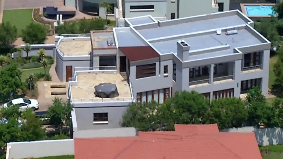 This file aerial image taken from video provided by VNS24/7 on Thursday, Feb. 14, 2013, shows the home of Olympic athlete Oscar Pistorius in a gated housing complex in Pretoria, South Africa. Oscar Pistorius is selling the house where Reeva Steenkamp was kiiled to raise money for his legal bills, and has still never returned to the upscale villa since the day he shot his girlfriend in an upstairs bathroom over a year ago, the athlete's lawyer said Thursday. (AP / VNS24/7-File)