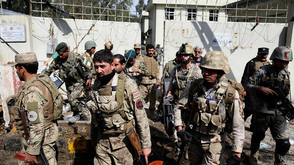 Afghan Army and police search through a police station after the Taliban staged a multi-pronged attack on a police station in Jalalabad, eastern Afghanistan, Thursday, March 20, 2014. (AP / Rahmat Gul)