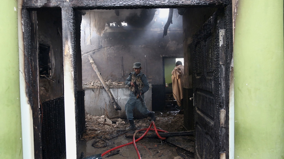 An Afghan police officer walks around inside the nearby state-run Afghan radio and television building badly damaged when a suicide car bomber blew up his vehicle near a police station in Jalalabad, Afghanistan, Thursday, March 20, 2014. (AP / Rahmat Gul)