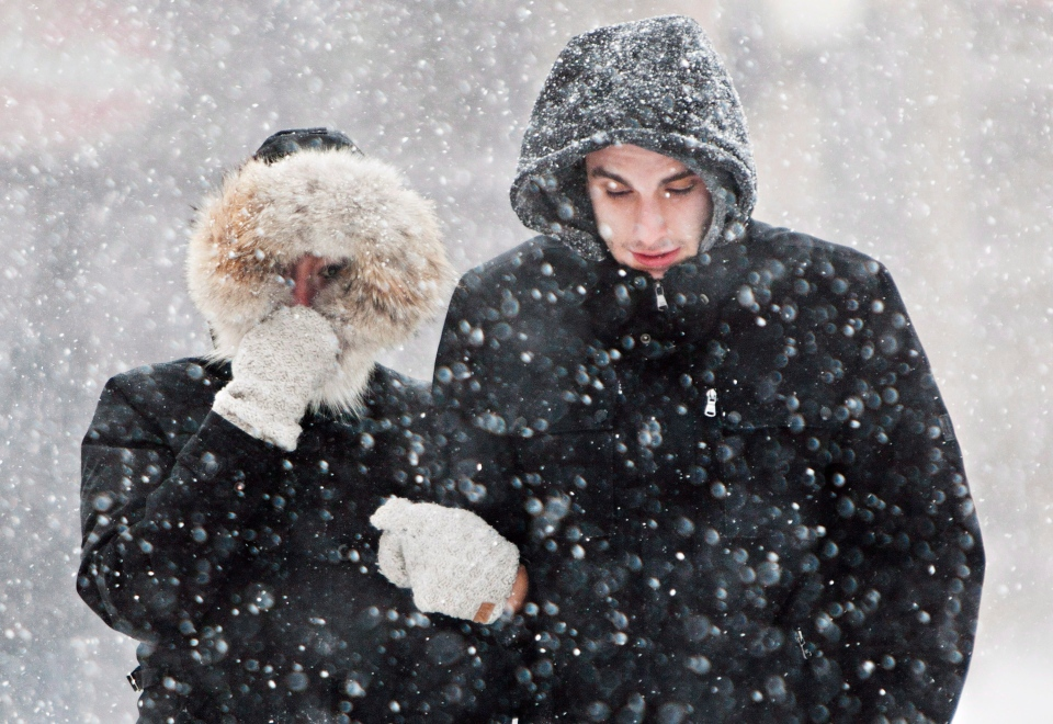 A couple shields themselves from blowing snow on Clifton Hill in Niagara Falls, Ont., during a snow storm Wednesday, March 12, 2014. (Aaron Lynett / THE CANADIAN PRESS)