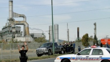 A police officer directs traffic as workers survey a fire that was caused by an explosion at the Co-op Refinery-Upgrader Complex in Regina on Thursday.