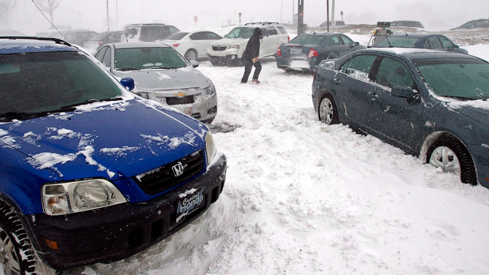 A stranded traveller crosses a parking lot at a service station in Borden-Carleton, Prince Edward Island on Sunday, Feb. 16, 2014. (Andrew Vaughn / THE CANADIAN PRESS)