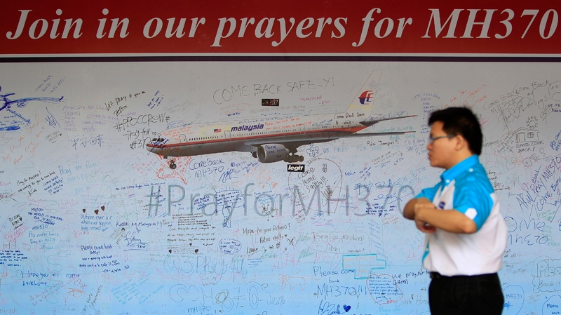 A man walks past a message board for passengers aboard a missing Malaysia Airlines plane, at a shopping mall in Petaling Jaya, near Kuala Lumpur, Malaysia, Friday, March 21, 2014. (AP / Lai Seng Sin)