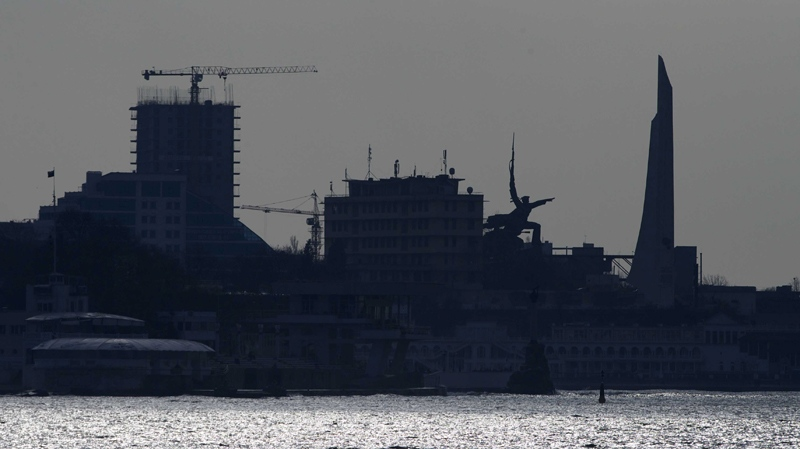 A Russian flag flies over a building as Sevastopol buildings and monuments are silhouetted in Crimea, on Thursday, March 20, 2014. (AP Photo/Ivan Sekretarev)