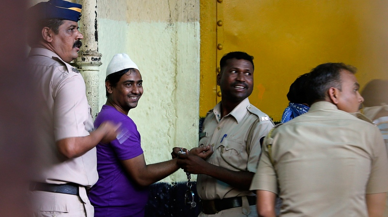 One of the four convicted, second left, smiles as he is escorted away by police officers along with three other who are convicted of the gang rape of a photojournalist in India's financial capital last year, in Mumbai, India, Thursday, March 20, 2013. (AP Photo/Rajanish Kakade)