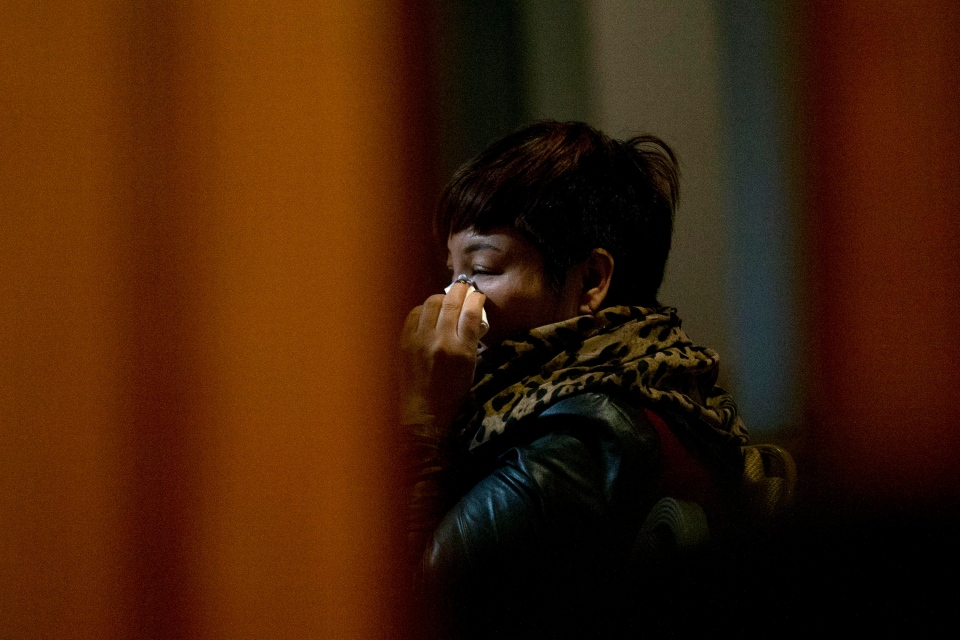 One of the relatives of Chinese passengers aboard missing Malaysia Airlines Flight MH370 wipes her tears as she watches a TV news program about the missing flight after a briefing meeting with Malaysian officials in a hotel ballroom in Beijing, China, Friday, March 21, 2014. (AP / Alexander F. Yuan)