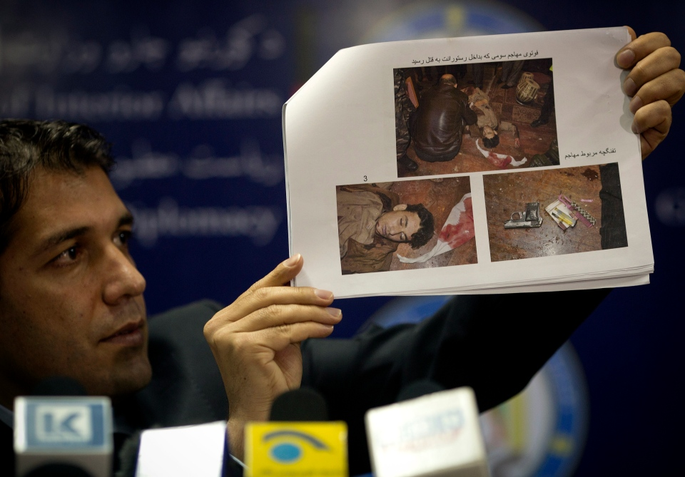 Sediq Sediqi, spokesman for the Afghan interior ministry, shows pictures of a dead gunman and his weapon, taken inside the Serena hotel after an attack on Thursday, during a press conference at the interior ministry in Kabul, Afghanistan, Friday, March 21, 2014. (AP / Anja Niedringhaus)