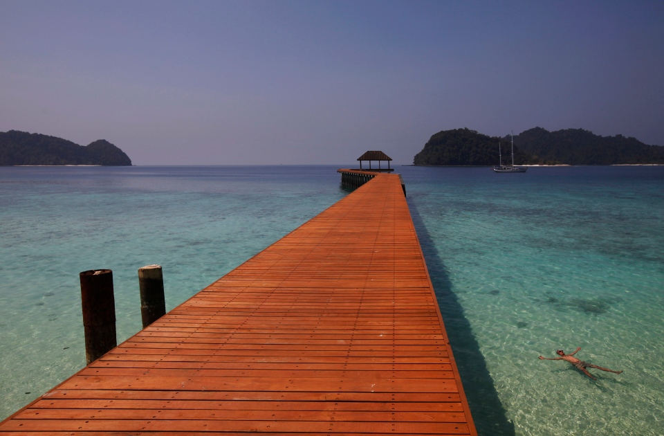 A tourist floats on sparkling clear water next to a newly built jetty on the Chin Kite Kyunn, or Mosquito Bite Island, in Mergui Archipelago, Myanmar. (AP / Altaf Qadri)