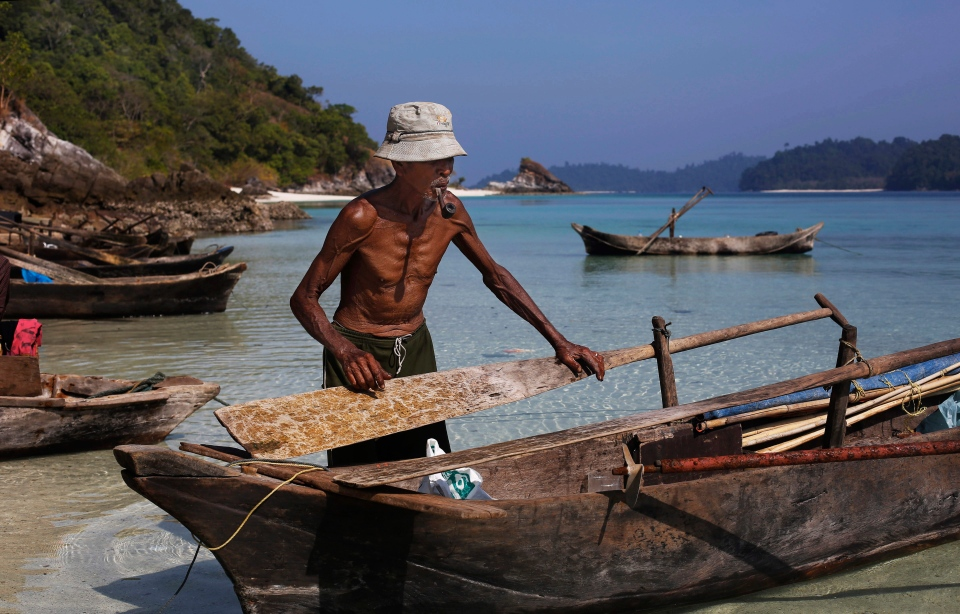 Maali, an elderly Moken man, nomads of the sea, smokes a pipe as he adjusts a paddle on his canoe on Island 115 in Mergui Archipelago, Myanmar. (AP / Altaf Qadri)