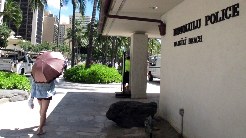 A pedestrian walks in front of a Honolulu Police Department station in Waikiki on Wednesday, March 19, 2014. (AP Photo/Oskar Garcia)
