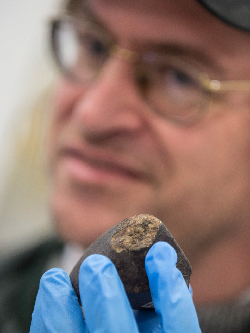 Phil McCausland, an Assistant Professor and Meteorite Curator at Western's Department of Earth Sciences holds a meteorite, the approximate size of the one which they suspect hit the ground just north of St. Thomas, Ont. on Tuesday, during a press conference at the airport in St.Thomas, Friday, March 21, 2014. (Geoff Robins / THE CANADIAN PRESS)