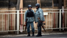 Afghan policemen patrol Afghan hotel after attack