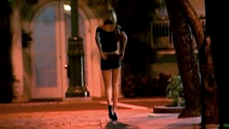 A sex worker walks down the street.