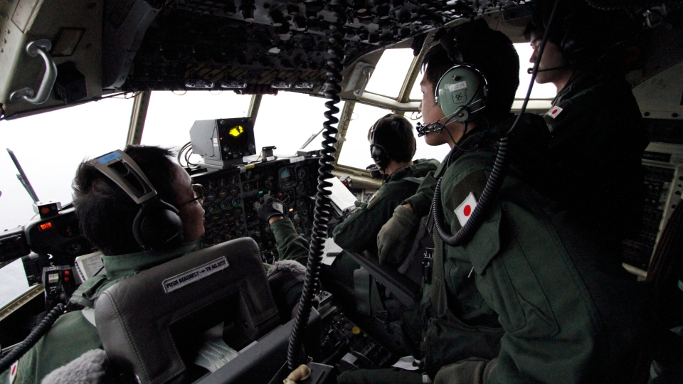 Japanese Air Self-Defense Force's Capt. Junichi Tanoue, left, co-pilot Ryutaro Hamahira, second from left, and engineer Noriyuki Yamanouchi, second from right, scan the ocean aboard a C130 aircraft while it flies over the southern search area in the southeastern Indian Ocean, 200 to 300 kilometers (124 to 186 miles) south of Sumatra, Indonesia, Friday, March 21, 2014. (AP / Koji Ueda)