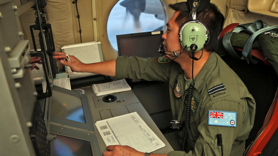 Flight Officer Jack Chen mans the navigation and communication station on board a Royal Australian Air Force AP-3C Orion as they search for missing Malaysia Airlines flight MH370 in southern Indian Ocean, Australia, Saturday, March 22, 2014. (AP / Rob Griffith/Pool)