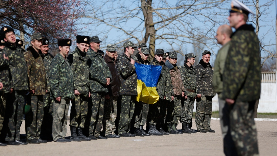 Ukrainian servicemen, holding a Ukrainina flag, sing a national anthem at the Novofedorivka base after it was stormed, some 50 km (30 miles) west of Simferopol, Crimea, Saturday, March 22, 2014. (AP / Max Vetrov)