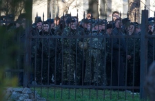 Ukrainian officers stand behind the fence of the B