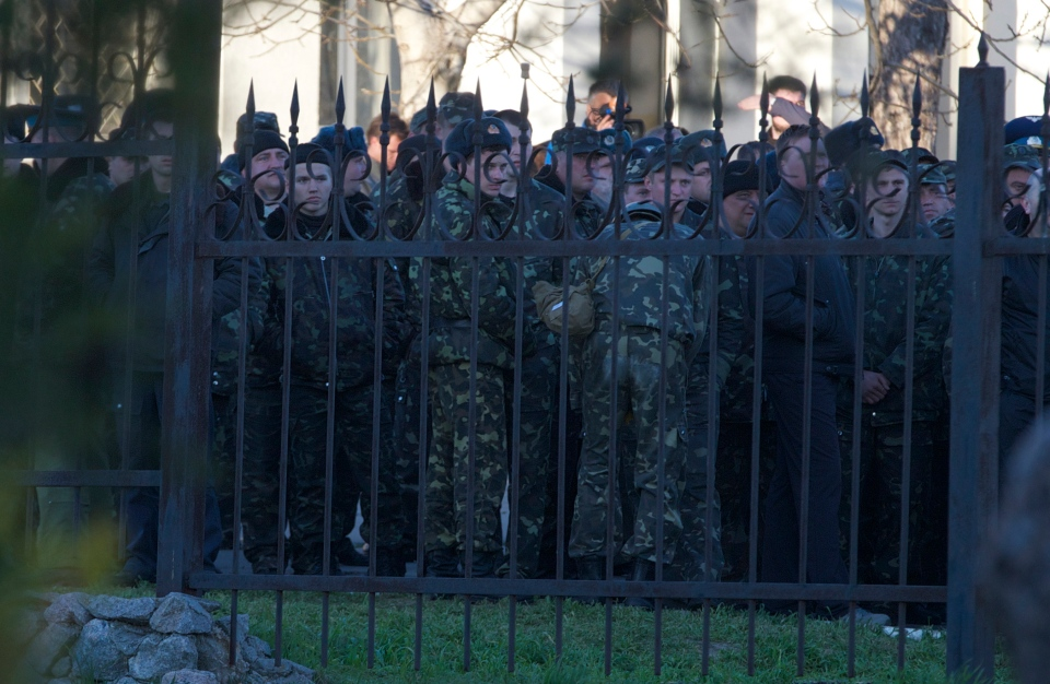 Ukrainian officers stand behind the fence of the Belbek airbase after Russians took control, outside Sevastopol, Crimea, on Saturday, March 22, 2014. (AP / Ivan Sekretarev)
