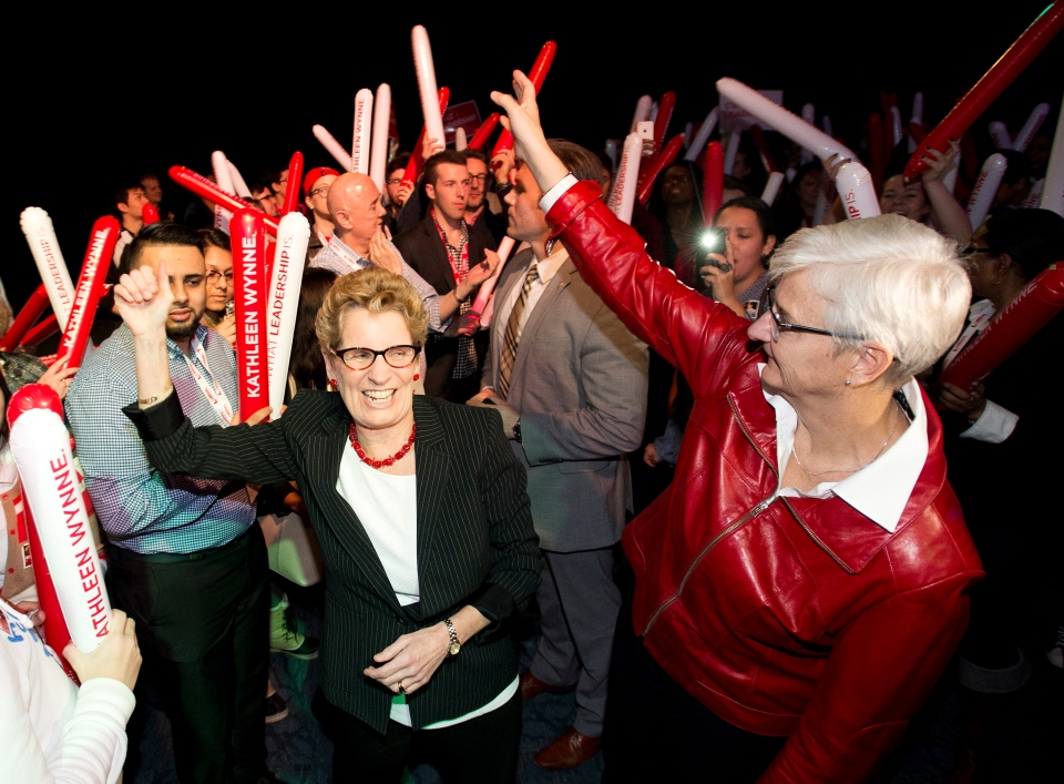 Ontario Premier Kathleen Wynne, left, and her partner Jane Rounthwaite, right, greet supporters and her caucus at a rally during the party's annual general meeting in Toronto on Saturday, March 22, 2014. (Nathan Denette / THE CANADIAN PRESS)