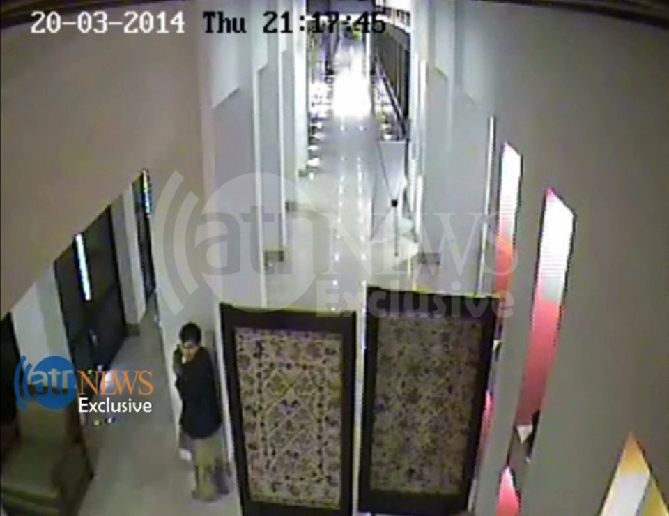 In this frame grab provided from a video by Ariana Television News, an attacker hides with his small pistol outside the restaurant near the bathrooms of the Serena hotel in Kabul, Afghanistan, Thursday, March 20, 2014. (AP / Arian Television News )