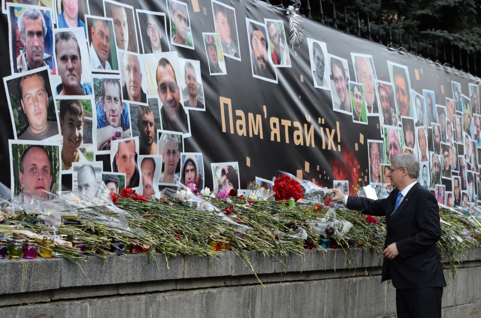 Prime Minister Stephen Harper lays a bouquet of flowers at a makeshift memorial on Hrushevsky Street in Kiev, Ukraine, on Saturday, March 22, 2014. (Sean Kilpatrick / THE CANADIAN PRESS)
