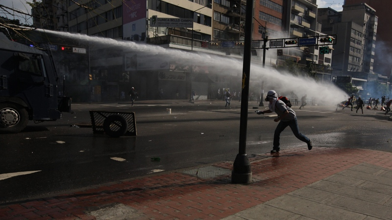 A masked anti-government protester throws a stone at a spraying water canon operated by Bolivarian National Police during clashes in Caracas, Venezuela, Saturday, March 22, 2014. (AP Photo/Fernando Llano)