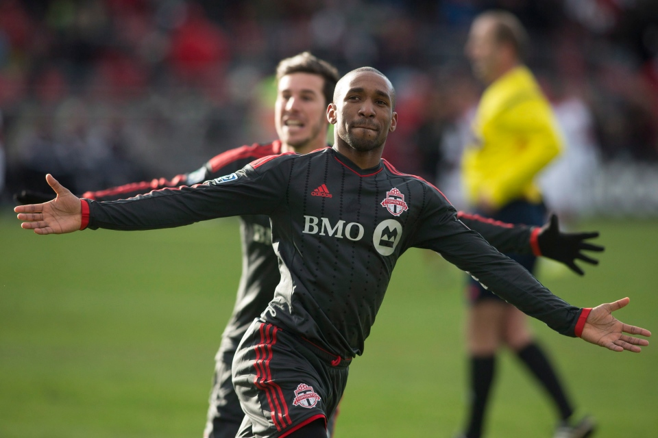 Toronto FC 's Jermain Defoe celebrates after scoring against D.C. United as Alvaro Rey (left0 runs in during second half MLS action in Toronto on Saturday March 22, 2014. THE CANADIAN PRESS/Chris Young