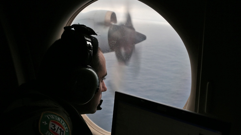 Flight officer Rayan Gharazeddine on board a Royal Australian Air Force AP-3C Orion, searches for the missing Malaysia Airlines Flight MH370 in southern Indian Ocean. (AP Photo/Rob Griffith, Pool)