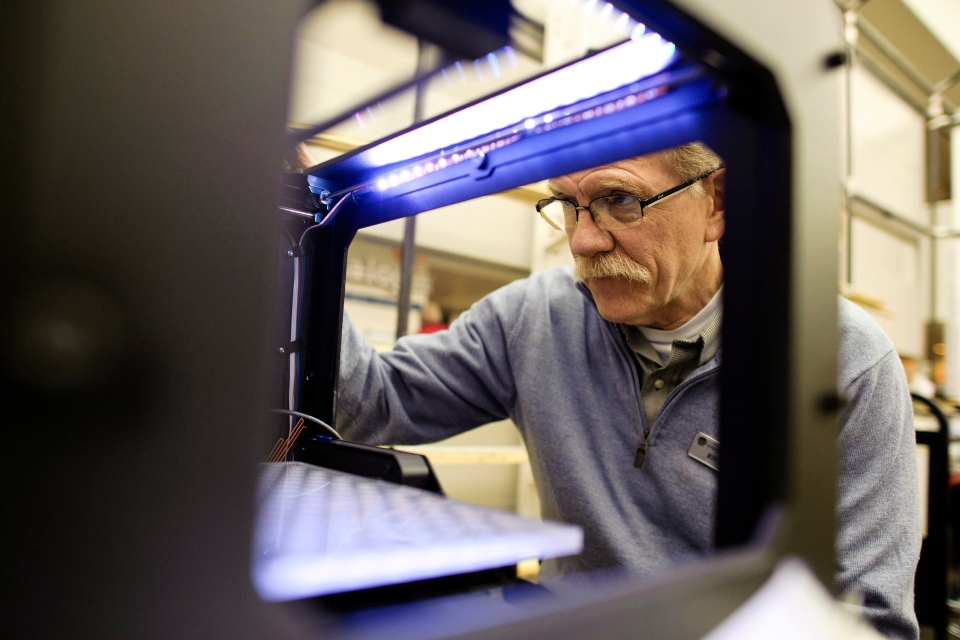 In this Jan. 29, 2013 photo, Bill Derry, Assistant Director of Innovation and User Experience at the Westport, Conn., Public Library, looks at the gears of a new 3D printer. (AP / Republican-American, Erin Covey)
