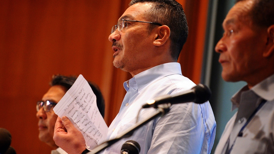 Malaysian Defense Minister Hishammuddin Hussein, center, shows a note from Chinese Ambassador to Malaysia Huang Huikang stating that they received a recent satellite image during a search of the missing Malaysia Airlines, flight MH370, half way through a press conference at a hotel in Sepang, Malaysia, Saturday, March 22, 2014. (AP / Joshua Paul)