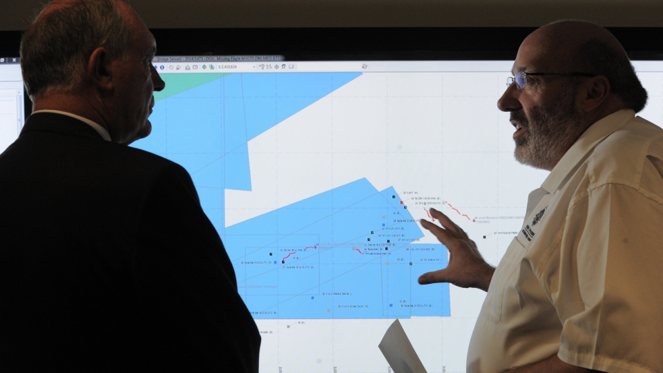 Mike Barton, rescue coordination chief, right, shows Australia's Deputy Prime Minister, Warren Truss, the map of the Indian Ocean search areas during a tour of the Australian Maritime Safety Authority's rescue coordination center in Canberra, Sunday, March 23, 2014. (AP / Graham Tidy)