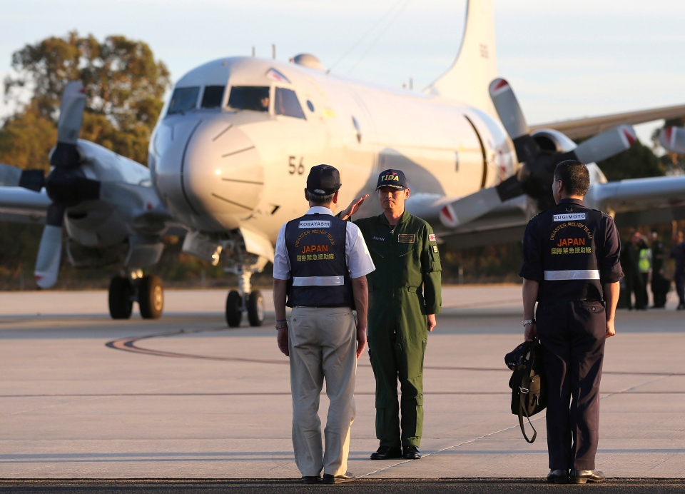 Japanese Commander Hidetsugu Iwamasa salutes Japan's Disaster Relief Team leader Masahiko Kobayashi, left, after his P-3C Orion from Japan Maritime Self-Defense Force arrived at Royal Australian Air Force Pearce Base in Perth, Australia, Sunday, March 23, 2014. (AP / Rob Griffith, Pool)