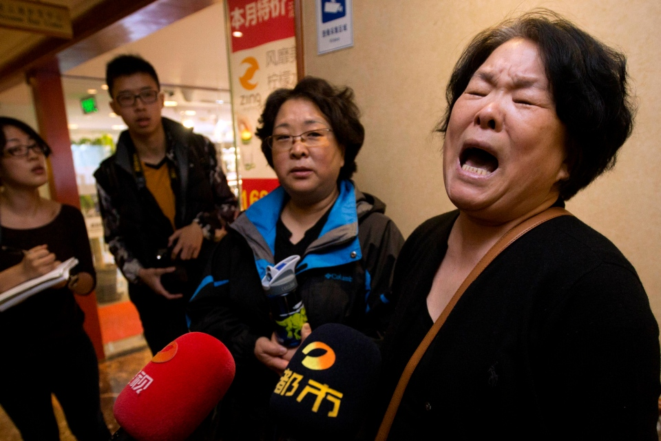 A relative of Chinese passengers aboard the missing Malaysia Airlines, MH370, expresses her frustration at the lack of information to journalists in Beijing, China, Sunday, March 23, 2014. (AP / Ng Han Guan)