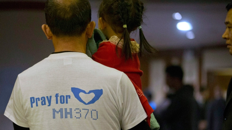 A relative of Chinese passengers aboard the missing Malaysia Airlines, MH370, wears a t-shirt with the words 'Pray for MH370' in Beijing, China, Sunday, March 23, 2014. (AP Photo/Ng Han Guan)