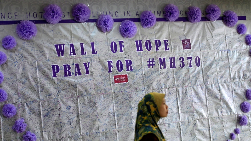 In this March 23, 2014 photo, a woman walks past a message board for passengers aboard a missing Malaysia Airlines plane, at a shopping mall in Kuala Lumpur, Malaysia. (AP / Lai Seng Sin)