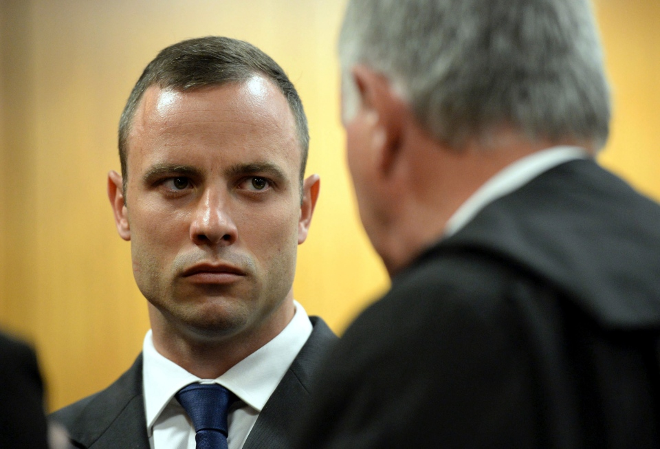 Oscar Pistorius talks to to his defense attorney Barry Roux before the proceedings get under way at the high court in Pretoria, South Africa on March 24, 2014. (AP / Chris Collingridge)