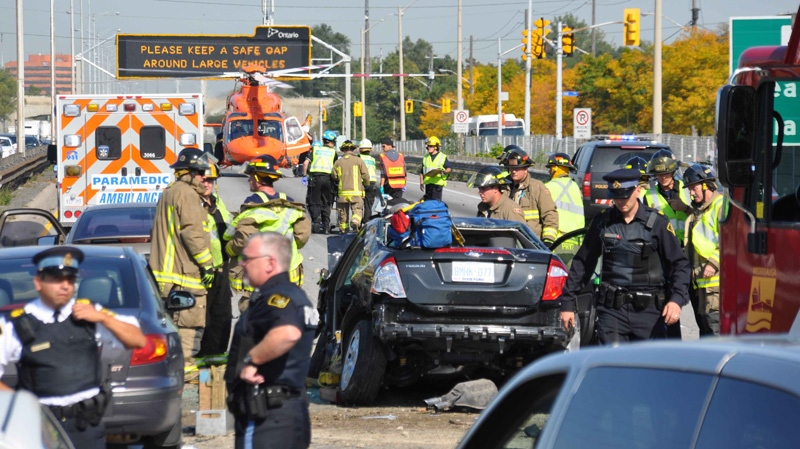 Firefighters and police officers surround a damaged car after a serious accident on the QEW on Friday, Oct. 7, 2011. (Andrew Collins for CTV News)