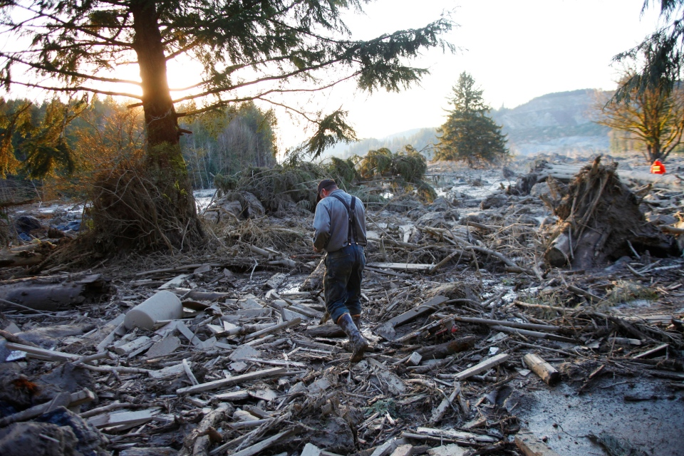 Steve Skaglund walks across the rubble on the east side of Saturday's fatal mudslide near Oso, Wash., on March 23, 2014. (The Herald / Genna Martin)