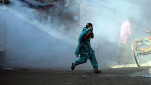 A Bangladeshi garment worker runs for cover amid tear gas fired by police as they gathered for a protest in front of a closed factory in Gazipur, on the outskirts of Dhaka, Bangladesh, Tuesday, Nov. 19, 2013. (AP / A.M. Ahad)