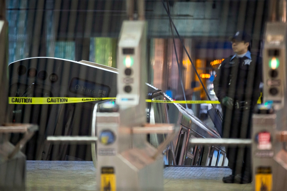 A police officer stands near a Chicago Transit Authority train car that derailed at the O'Hare Airport station early Monday, March 24, 2014. (AP / Andrew A. Nelles)