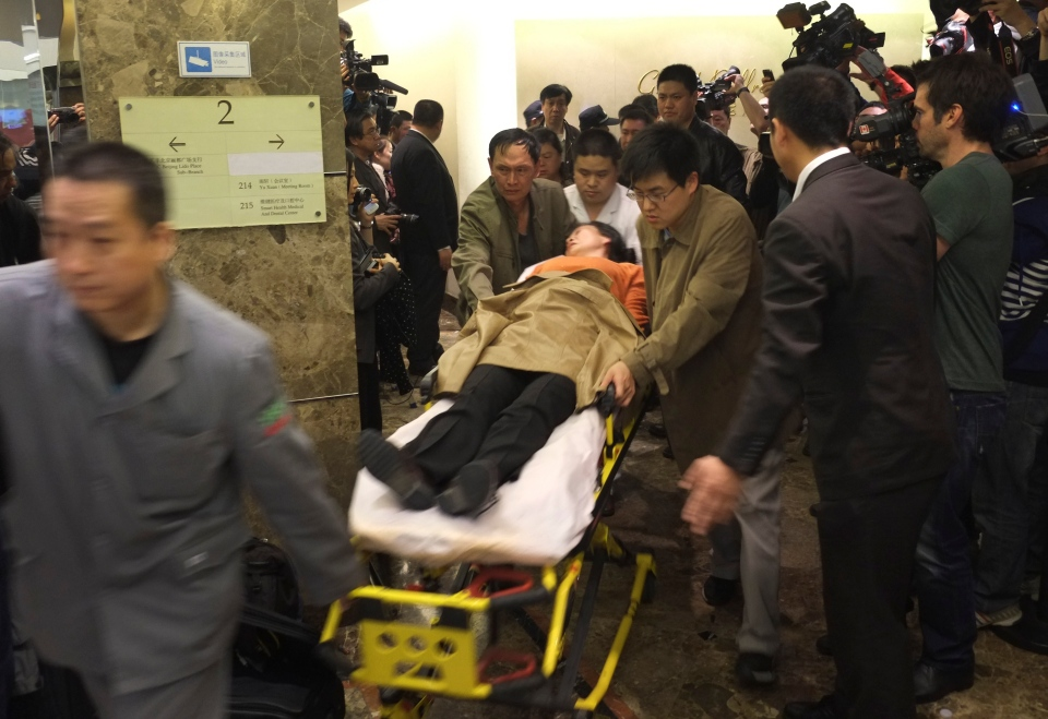 Medical personnel and people use a stretcher to carry out a woman who fainted after the announcement by the Malaysian government that the missing Malaysia Airlines airliner MH370 had crashed in the Indian Ocean, from a hotel ballroom in Beijing, China, Monday, March 24, 2014. (AP Photo)
