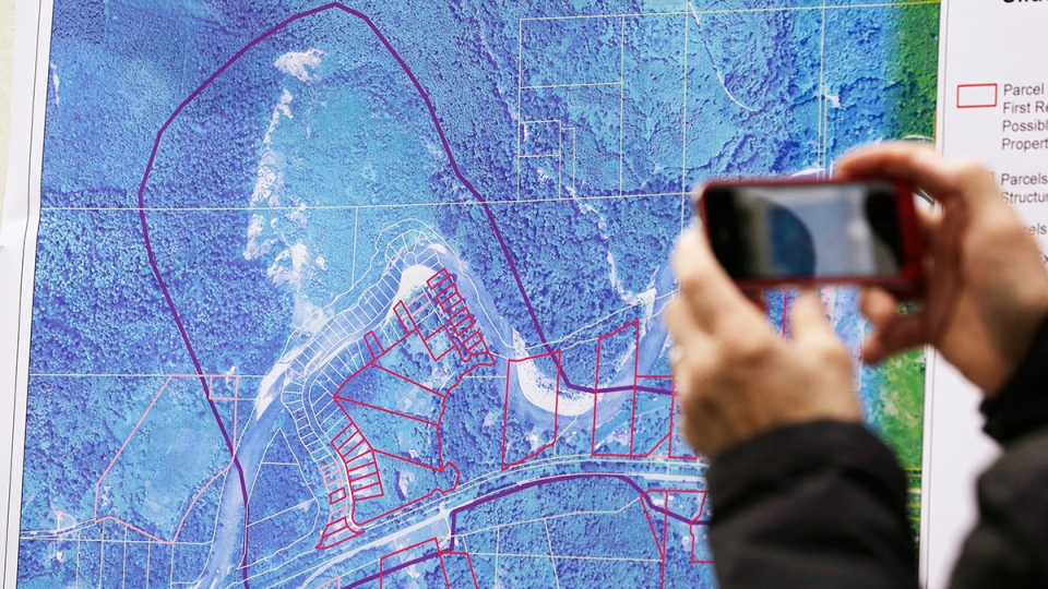 A news person photographs a map showing the location of a deadly mudslide that happened two days earlier, before a news conference, in Arlington, Wash., Monday, March 24, 2014. (AP / Elaine Thompson)