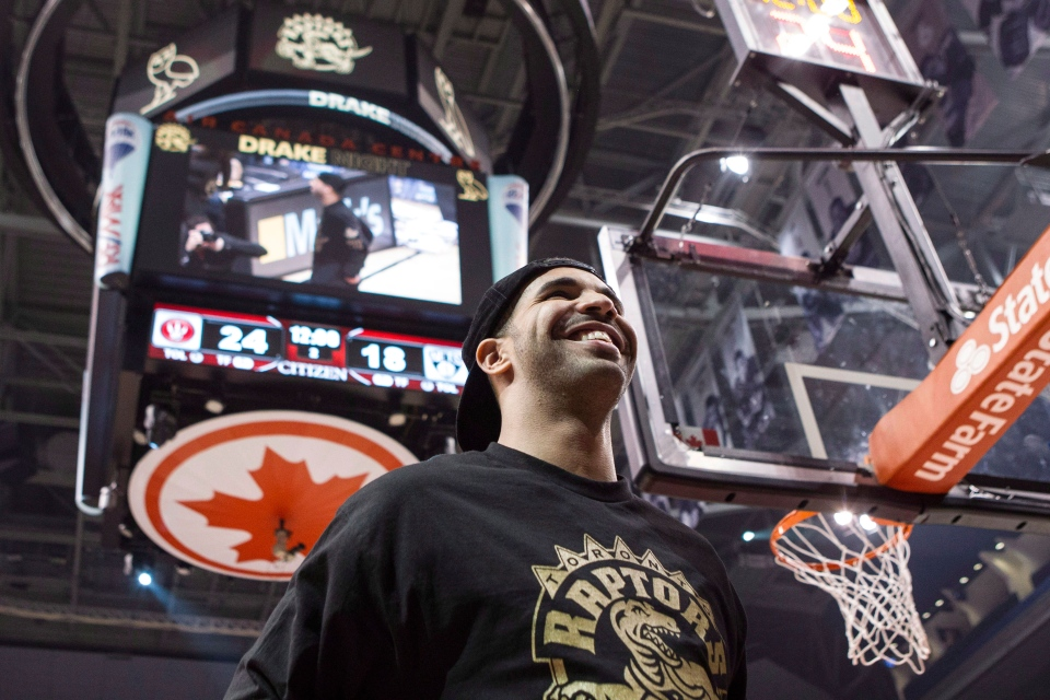 Rapper Drake stands on the court at the end of the first quarter as Toronto Raptors take on Brooklyn Nets in NBA basketball action in Toronto on Saturday, January 11, 2014. (Chris Young / THE CANADIAN PRESS)