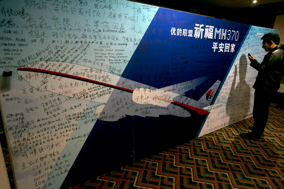 """A man uses his mobile phone near a board with the characters """"Pray for MH370 safe return"""" meant for relatives and workers to write their prayers and well wishes on in a room reserved for relatives of Chinese passengers aboard the missing Malaysia Airline jet in Beijing, China, Monday, March 24, 2014.  (AP / Ng Han Guan)"""
