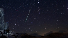 A meteor explodes across night sky